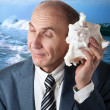 Stock Photo: Businessman listening to the shell