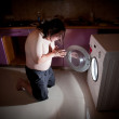 Asian fat man kneel in prayer by washing machine — Stock Photo