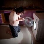 Asian fat man kneel in prayer by washing machine — Stock Photo