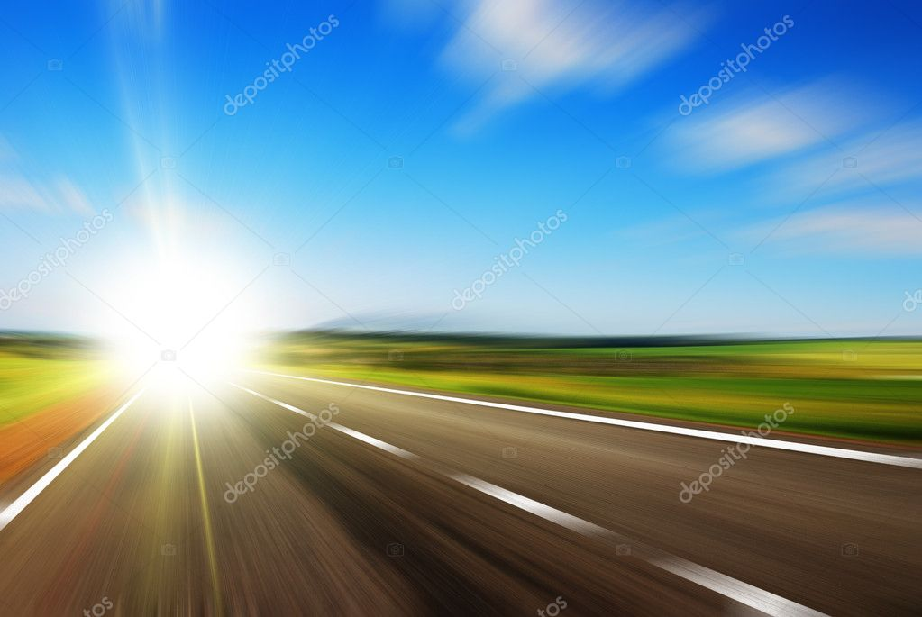 Blurred road and blue blurred sky with a shining sun — Stock Photo #4540365