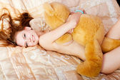 Woman with a teddy bear on bed — Stock Photo