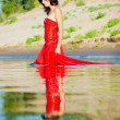 Royalty-Free Stock Photo: Woman in red dress on coast