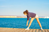 Woman get fitness on sea — Stock Photo