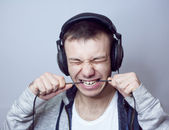 Guy with headphones eats cable — Stock Photo