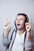 Guy in headphones listens music — Stock Photo
