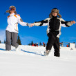 Happy skiers hurry on snow — Stock Photo