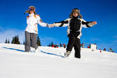 Happy skiers hurry on snow — Stock Photo