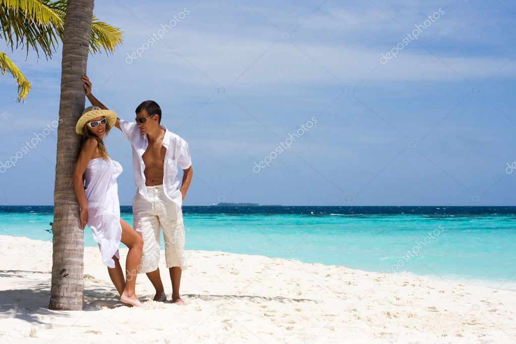 A happy young couple on a beach  Stock Photo #4562351