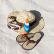 A hat, glasses and sandals lie on sand - Stock Photo