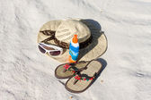 A hat, glasses and sandals lie on sand — Stock Photo