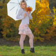 Blonde with an umbrella in autumn park — Stock Photo