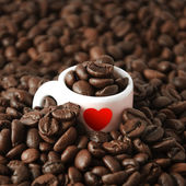 Coffee cup with heart in coffee beans — Stock Photo