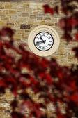 Clock on stone wall — Stock Photo