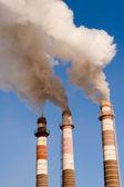 Three smokestack tube against the blue sky — Stock Photo