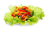 Mix of fresh vegetables from a colored paprika on leaves of green salad — Stock Photo