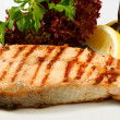Grilled salmon steak with salad and lemon - Stock Photo