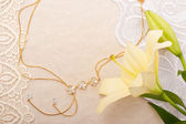 Chain and lily on lace background — Stock Photo