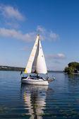 Uno yacht con vele bianche galleggianti nel lago — Foto Stock