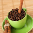 Coffee beans and cinnamon stick in a green cup — Stock Photo