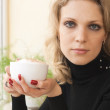 Portrait of a young blonde beauty with a cup of cappuccino — Stock Photo