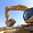 Stock Photo: Back hoe vehicle on pile of dirt