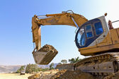 Back hoe vehicle on a pile of dirt — Stock Photo