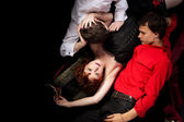 Red woman and two men - decadence style — Stock Photo