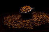 Dark cup with coffee beans — Stock Photo