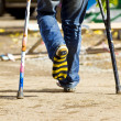 Color crutch and broken leg in striped sock — Stock Photo