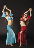 Two woman dance and smile in arabian costume — Stock Photo