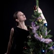 Young woman decorate christmas tree — Stock Photo