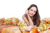 Młoda kobieta leżała na kolor poduszki i patrzeć na Ciebie — Zdjęcie stockowe
