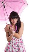 Girl freeze under rose umbrella in summer dress — Stock Photo