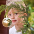 Adorable little girl looking out of a christmas tree — Stock Photo