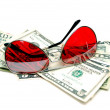 Red sunglasses resting on cash — Stock Photo