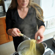 Woman cooking spaghetti noddles - Foto de Stock