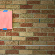 Note taped on brick wall — Stock Photo