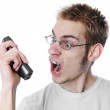 Angry young man screams into phone — Stock Photo