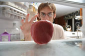 Man snatching apple from fridge — Stock Photo