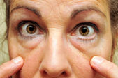 Middle Aged Woman Pointing at her eyes closeup — Photo