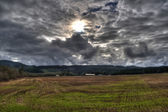 Empty Grass Field With Sun Bursting Through A Dark Overcast Cloud Cover — Stock Photo