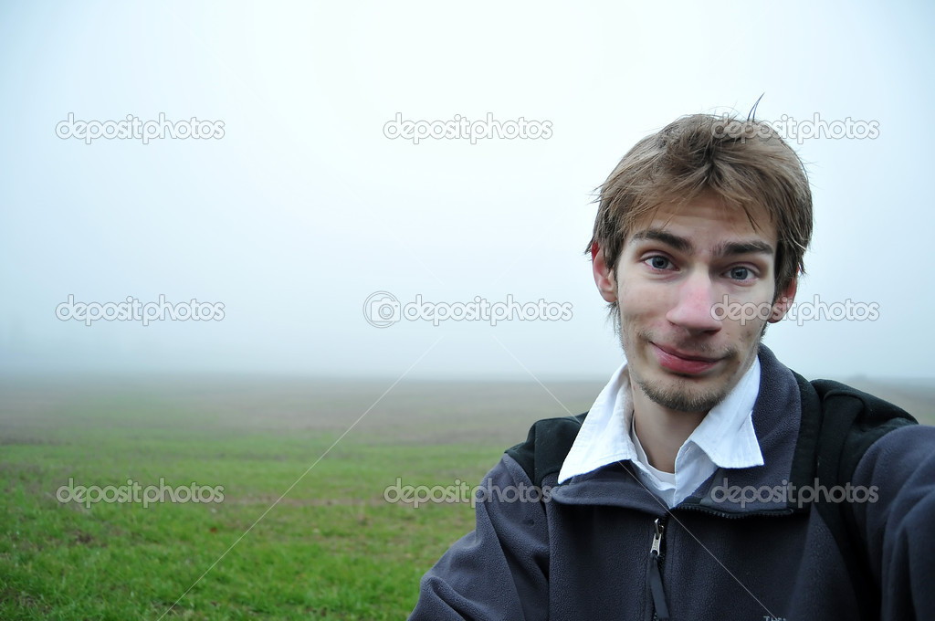 A young adult stands in a green foggy field looking at the camera with a smile. this makes a good background — Stock Photo #4627387
