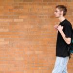 Student walking besides brick wall — Stock Photo
