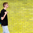 Student walking besides brick wall — Stock Photo