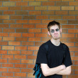 Student leaning against brick wall — Stock Photo