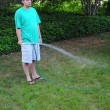 Man watering his grass lawn with a hose — Stock Photo