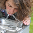 Teenager drinks from a drinking fountain — Stock Photo