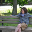Stock Photo: Homeless youth sits on bench