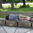 Sleeping on a bench in a public park - Stock Photo