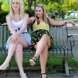 Royalty-Free Stock Photo: Two girl friends sitting on a bench